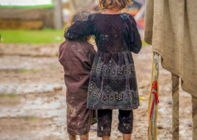 Two siblings standing in the mud after rain