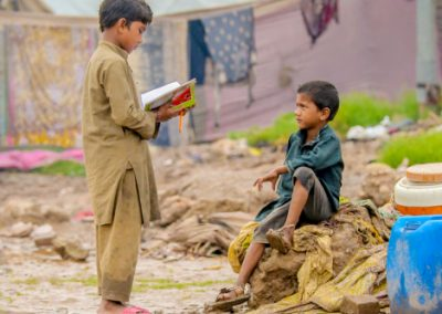 Slum school student teaching his little brother after slum class