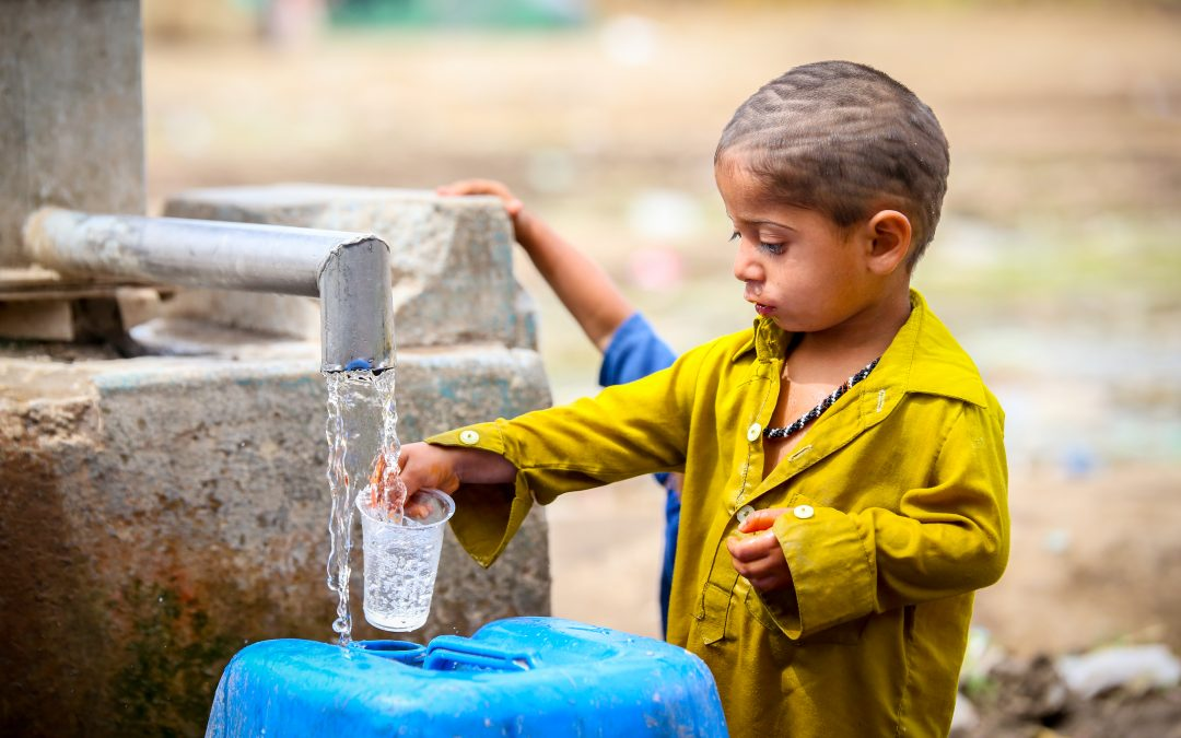 A Slum Child trying to gather some water in his glass